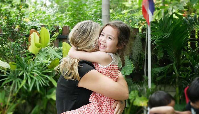 Happy child and teacher hug at British Early Years Centre International kindergarten in Bangok