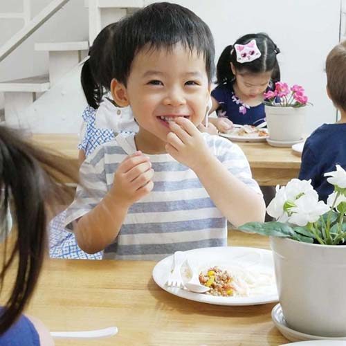 Child eating healthy food at British Early Years Centre International kindergarten in Bangok